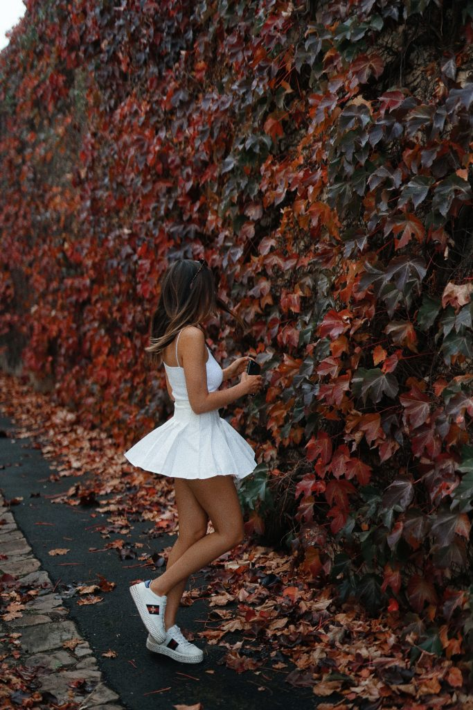 woman in white mini dress standing on red leaves